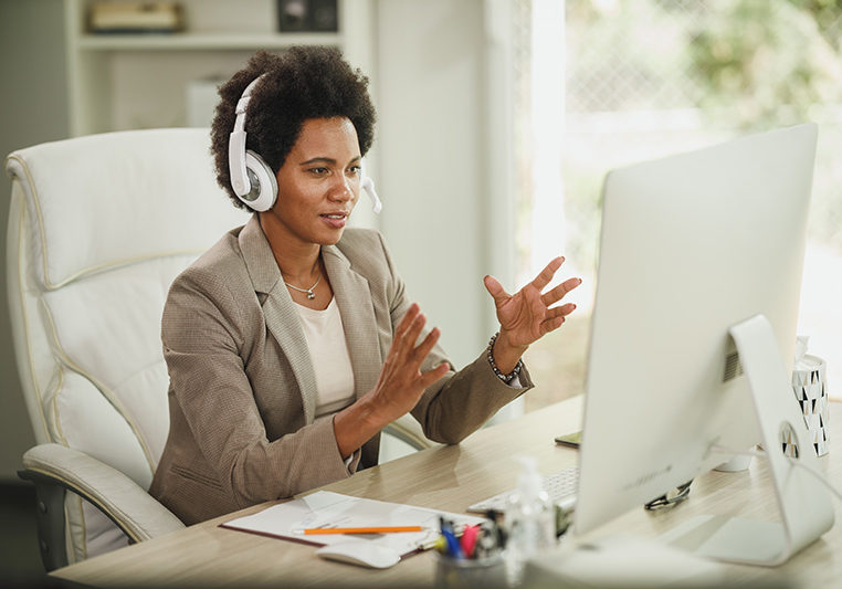 Shot of an attractive African businesswoman with headphones having video call while working on computer during corona virus pandemic.